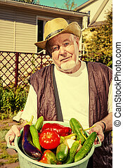 man with vegetables - Smiling senior man with his harvest in...