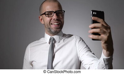 Funny businessman manager makes selfie phone. A man wearing...