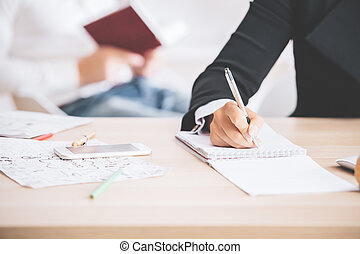 Woman writing in notepad - Closeup of woman hand writing in...