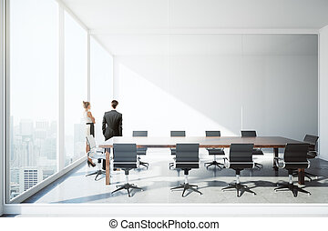 Businessman and woman in conference room - Thoughtful...