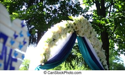 wedding arch decorated with cloth, flowers and word LOVE. Wedding settings