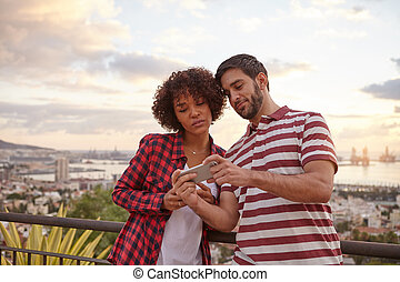 Two nice friends looking at a cellphone - Nice young couple...
