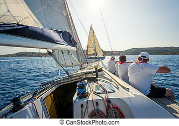 Onboard view of racing sailing yacht with a crew sitting on...