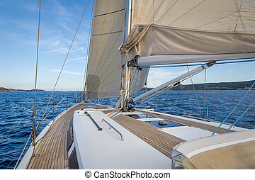 Sailing boat teak deck and hoisted sails, view from the...