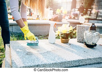 A woman cleans the grave. Washing tombstone with brush....