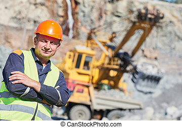 worker in front of heavy excavator and dumper truck - mining...