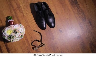 set of groom bow tie, boutonniere, and shoes lie on wooden...
