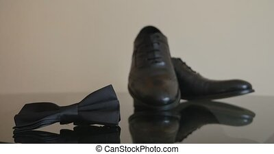 close-up of lightened with natural light men's shoes and bow...