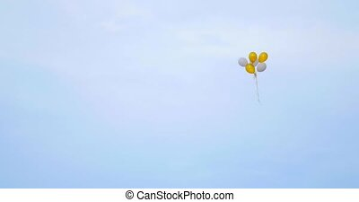 many bright baloons in the blue sky.