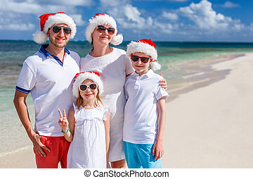Family at beach on Christmas - Happy beautiful family in red...