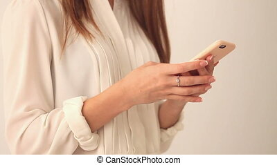 Woman using mobile phone - Young woman in white blouse using...