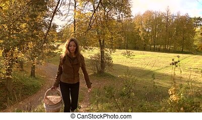 Brunette girl in brown jacket with a basket walking uphill in autumn woods. Climbing uphill. 4K steadicam shot