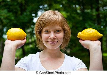 Girl holding lemons - A smiling girl holding two lemons...