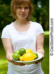 Girl holding a bowl of lemon and lime outdoors on a summer...