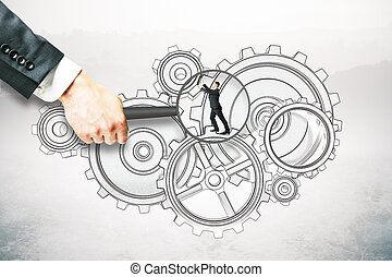 Teamwork concept - Hand holding magnifier over tiny...