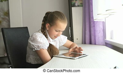 Schoolgirl uses a digital tablet computer at home - Little...