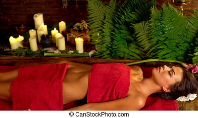 Woman lying in massage spa salon. Camera moves from face to...