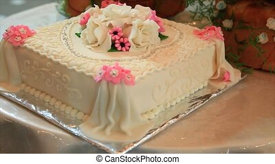Wedding cake decorated with white and pink roses.
