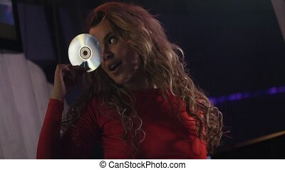 Dj girl in red dress hold CD disk at face at turntable in...