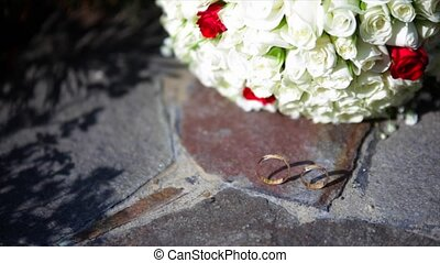 two wedding rings on a stone with pink flowers of a...