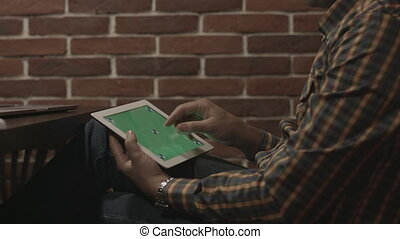 Man in plaid shirt uses touch screen tablet. - Side close-up...