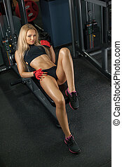 Brutal athletic woman resting on bench - Muscular body of a...