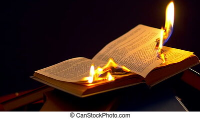 Open book burning on black background. Book with text...