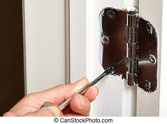 Door hinge installation. - Hands with screwdriver fixing a...