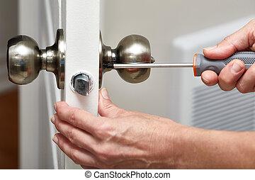 Door knob installation. - Hands with screwdriver fixing a...