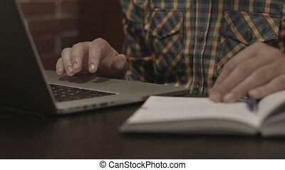 man in plaid shirt working at laptop in the cafe