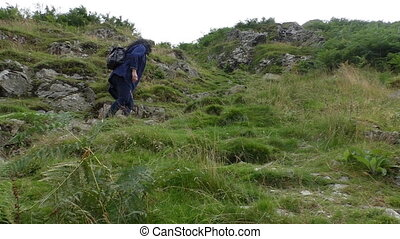 Woman climbing mountain slope - Woman with backpack climbing...