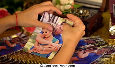 Female hands tearing love photos. Love is gone. On pictures...
