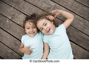 Hugging sisters in blue t-shirts over wooden ground
