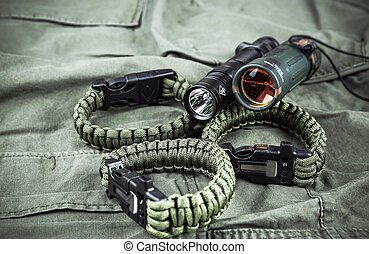 Military paracord bracelet, tactical torch and spy-glass on...