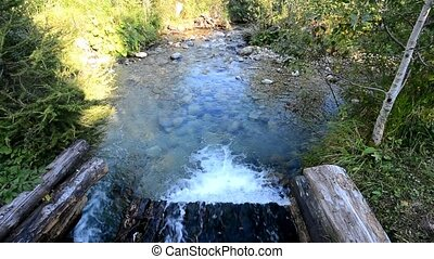 Flowing stream in gutter - Clear mountain stream flowing...