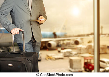 young business man using digital tablet with luggage in the...