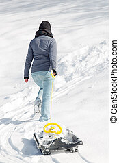 young woman pulling a sledge in the deep snow, backview - a...