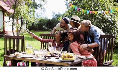 friends taking selfie at party in summer garden - leisure,...