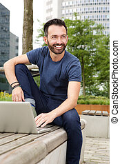 Relaxed mature guy sitting outdoors with laptop