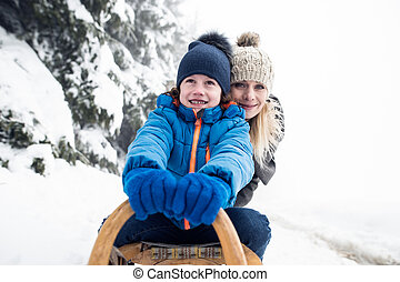 Mother with son on sledge. Foggy white winter nature. -...