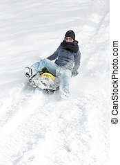 young woman sledging in the deep snow and have fun