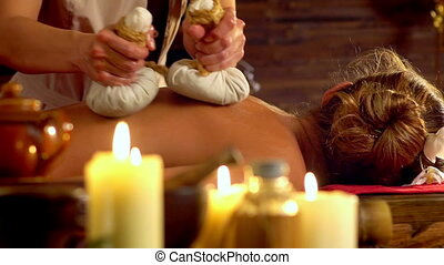 Young woman have hot poultice massage in spa salon with...