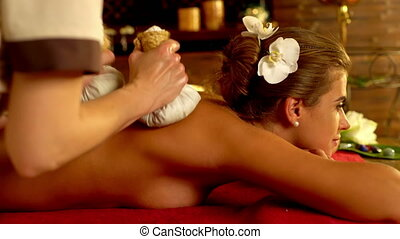 Young woman have hot exotic poultice massage in spa...