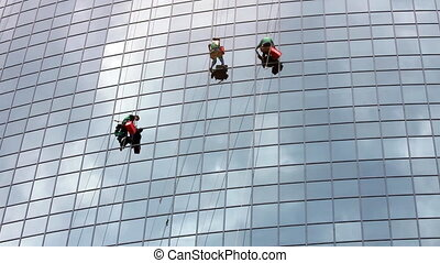 timelapse with window cleaners at work on skyscraper