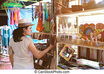 woman in souvenir shop - woman in colourful souvenir shop in...