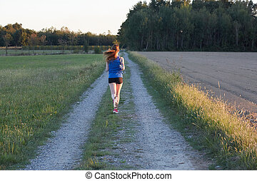 woman athlete running at sunset or