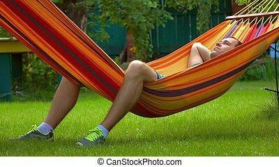 Man having rest in bright hammock - Man having rest in...