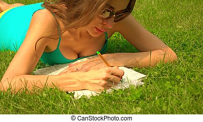 Beautiful brunette girl in sunglasses laying on the grass and colorizing