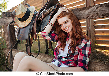 Happy woman cowgirl sitting on farm - Happy attractive young...