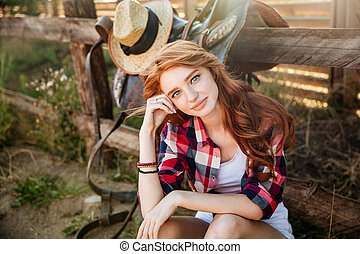 Woman cowgirl sitting and relaxing outdoors - Attractive...